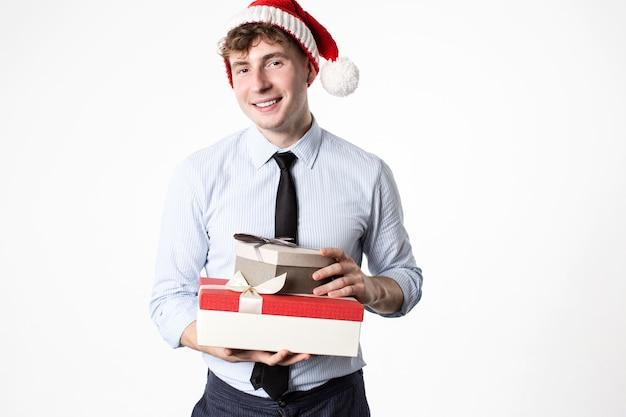 Hübscher lächelnder mann im weihnachtsmannhutmann mit geschenk