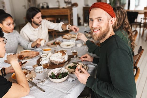 Hübscher lächelnder mann in der roten strickmütze mit bart, der glücklich am tisch sitzt