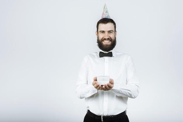 Hübscher lächelnder mann in einem weißen hemd und fliege in einer partykappe hält ein geschenk auf grau