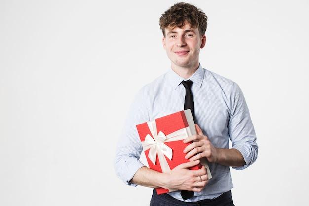 Hübscher lächelnder mann mit einem geschenk