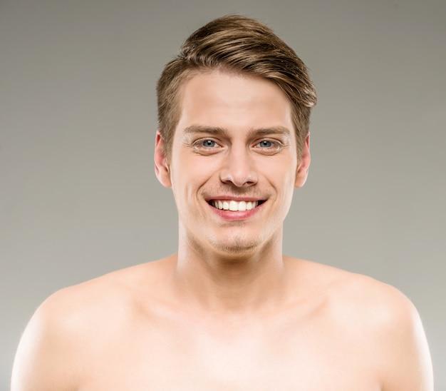Hübscher lächelnder mann mit reiner haut