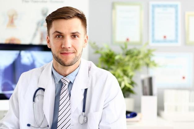 Hübscher lächelnder medizindoktor, der im büro sitzt