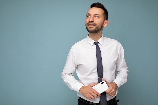 Hübscher lächelnder, nachdenklicher, gut aussehender, unrasierter mann mit bart, der ein lässiges weißes hemd und eine krawatte trägt, isoliert auf blauem hintergrund mit leerem raum, der das mobiltelefon in der hand hält und zur seite schaut