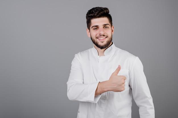 Hübscher lächelnder nahöstlicher junger doktor lokalisiert über grau