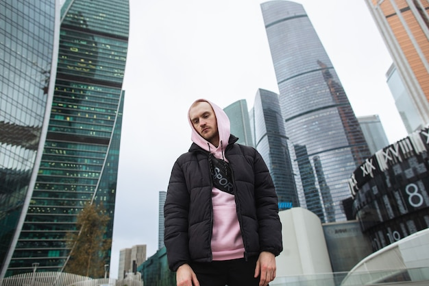 Hübscher lässiger mann in der schwarzen jacke und im rosa kapuzenpulli, die auf einer wolkenkratzeransicht stehen. moskau stadt.