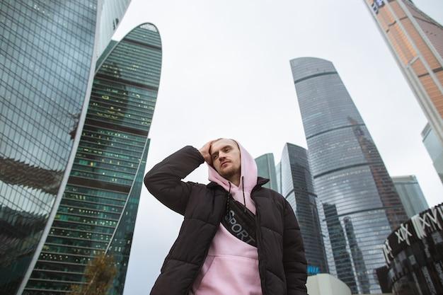 Hübscher lässiger mann in der schwarzen jacke und im rosa kapuzenpulli, die auf einer wolkenkratzeransicht stehen.