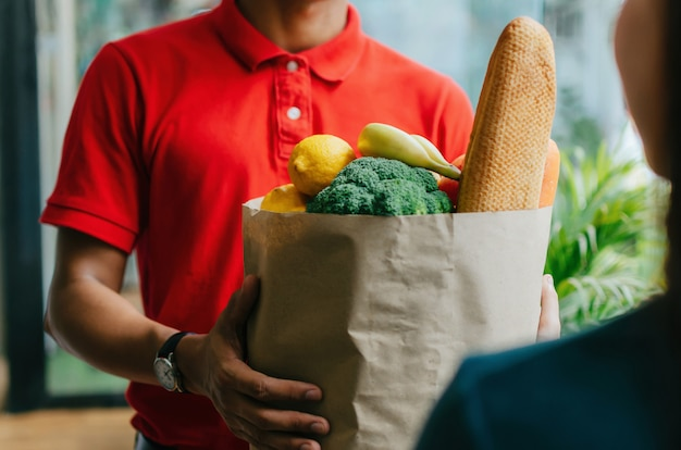 Hübscher lebensmittel-lieferservice-mann im roten hemd, der frische lebensmittel-set-tasche zum kunden an der tür nach hause hält, expresszustellung