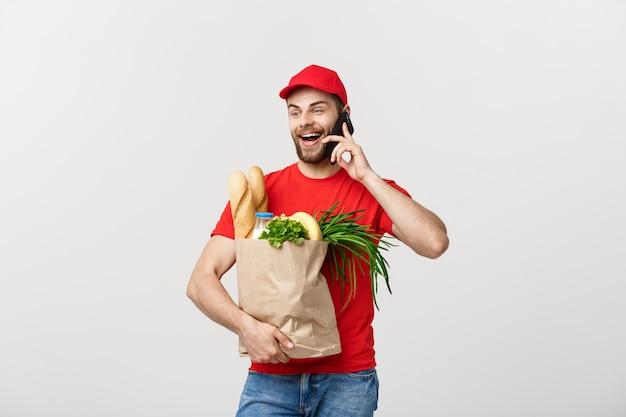 Hübscher lebensmittelgeschäftlieferer, der mit mobile spricht und lebensmittelgeschäftpapiertüte hält.