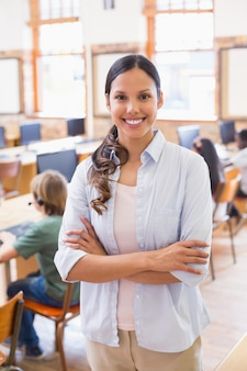 Hübscher lehrer, der an der kamera an der rückseite des klassenzimmers lächelt