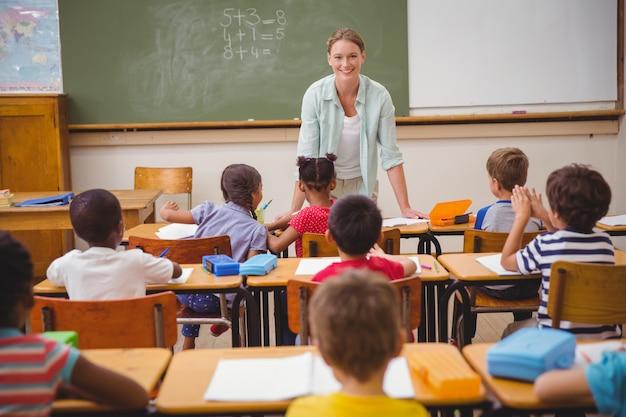 Hübscher lehrer, der mit den jungen schülern im klassenzimmer spricht