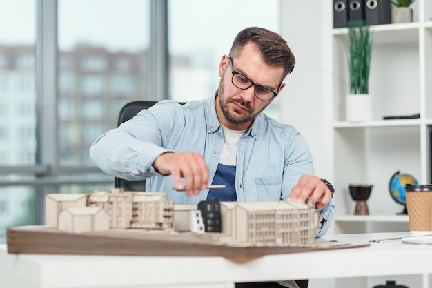 Hübscher leitender architekt bei brillen, der an einem bauprojekt arbeitet und das projekt eines wohnkomplexes untersucht, an dem er arbeitet.