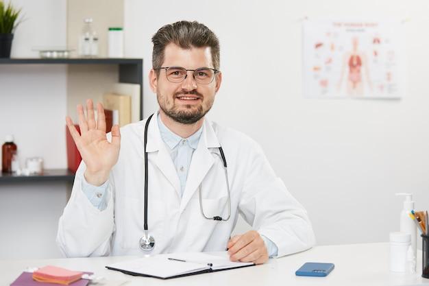 Hübscher leitender arzt, der hi geste zeigt, während er online arbeitet, bärtiger männlicher therapeut in weißer medizinischer uniform und brille, die im medizinischen kabinett mit stethoskop sitzen und videoanruf haben