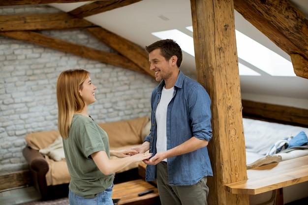 Hübscher liebevoller lächelnder freund beim händchenhalten der freundin in einer dachbodenwohnung