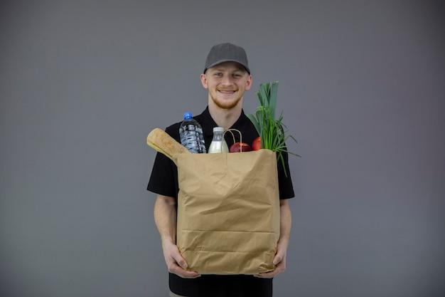 Hübscher lieferbote in der schwarzen uniform, die papiertüte des essens behandelt