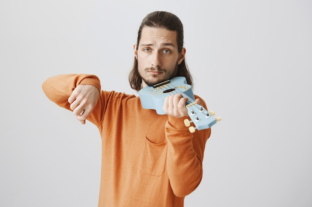 Hübscher lustiger kerl, der ukulele wie geige hält