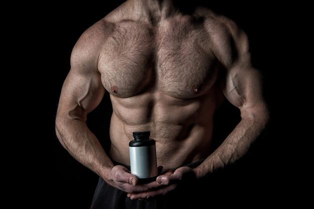 Hübscher macho-mann oder sexy muskulöser kerl mit athletenkörper und torso hält plastikglas oder behälter mit nahrung oder pillen auf schwarzem hintergrund