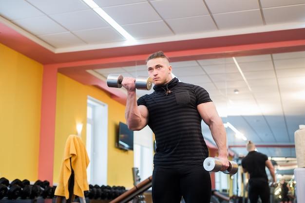Hübscher mächtiger athletischer mann, der langhantel-schulterpressübung macht. starker bodybuilder mit perfekten muskeln.
