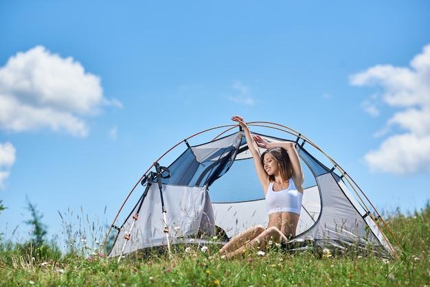Hübscher mädchenreisender, der im zelt sitzt, auf der spitze eines hügels gegen blauen himmel und wolken, mit geschlossenen augen lächelt, hände in die luft hebt, sonnigen tag in den bergen genießt