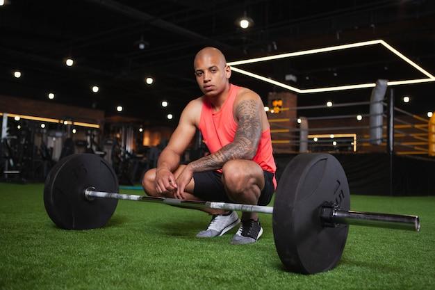Hübscher männlicher afrikanischer athlet, der an der turnhalle ausarbeitet