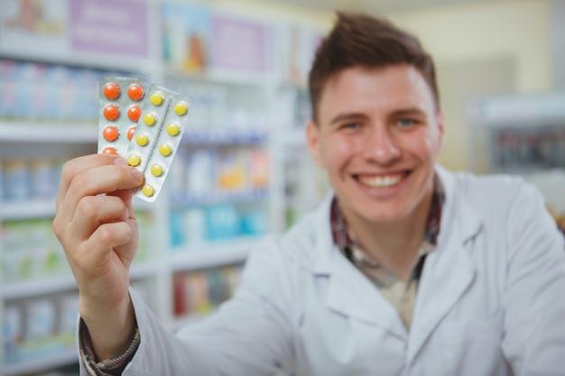 Hübscher männlicher apotheker, der an seiner drogerie arbeitet