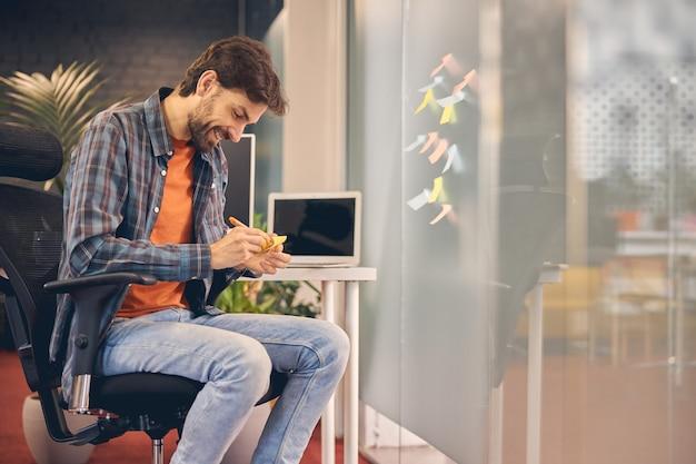 Hübscher männlicher arbeiter, der notizen macht und lächelt, während er in einem bequemen bürostuhl sitzt sitting