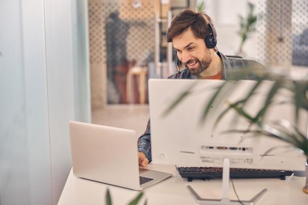 Hübscher männlicher arbeiter in headset sitzt am tisch mit desktop-pc und arbeitet am notebook