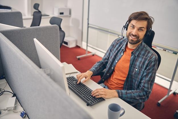 Hübscher männlicher arbeiter mit kopfhörer, der in die kamera schaut und lächelt, während er mit computer am bürotisch sitzt