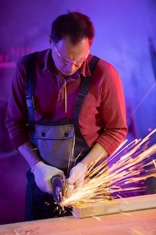 Hübscher männlicher arbeiter mittleren alters in jumpsuit-schutzbrille und handschuhen, die metall mit funken im farbigen licht in der garage schleifen