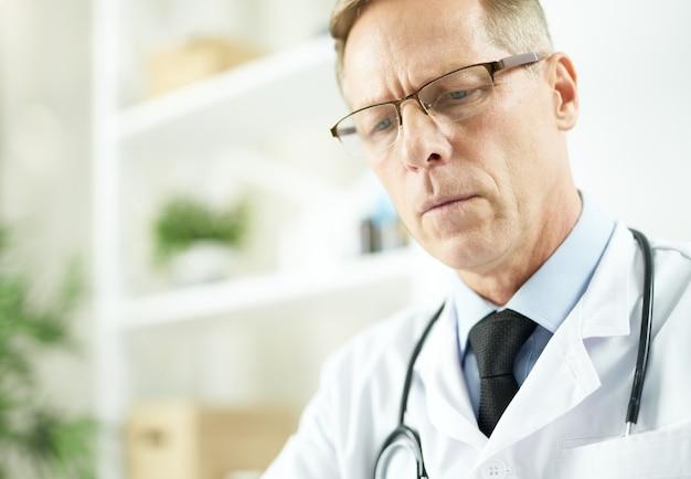 Hübscher männlicher arzt mit brille, der in der klinik arbeitet