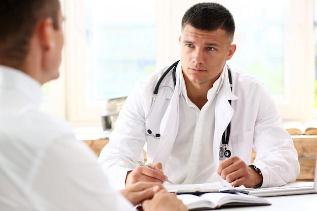 Hübscher männlicher arzt schüttelt hand als hallo mit patient im büro