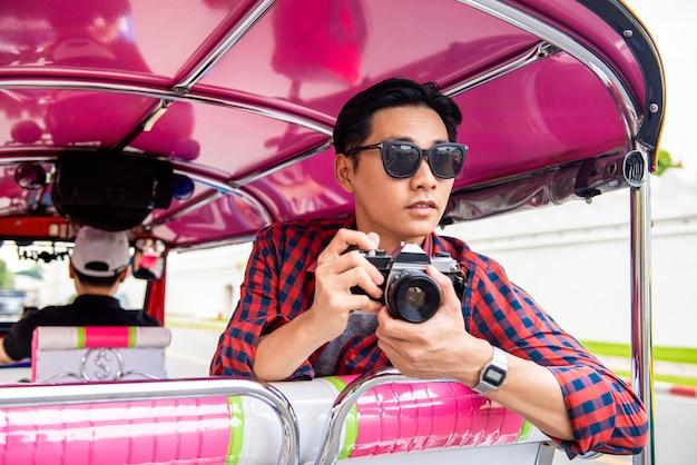 Hübscher männlicher asiatischer tourist, der kamera auf tuk-tuk-taxi in bangkok thailand während der sommerferien-alleinreisen hält