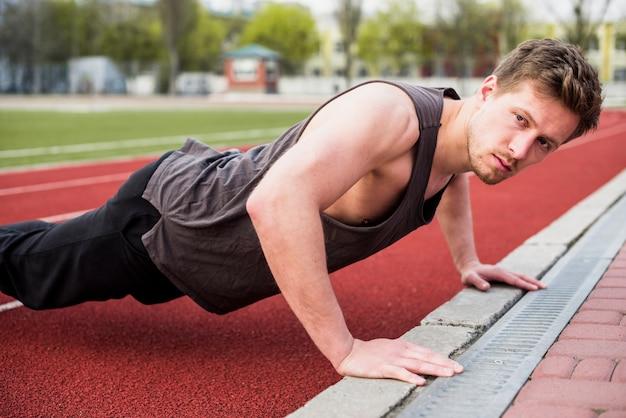 Hübscher männlicher athlet, der liegestütz auf rennstrecke tut
