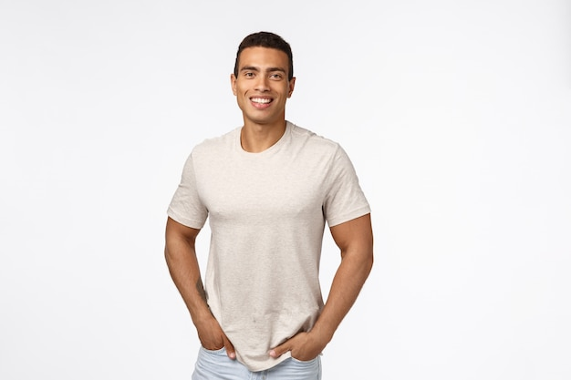 Hübscher männlicher athlet im zufälligen t-shirt, griffhände in den taschen und lächeln mit glücklichem