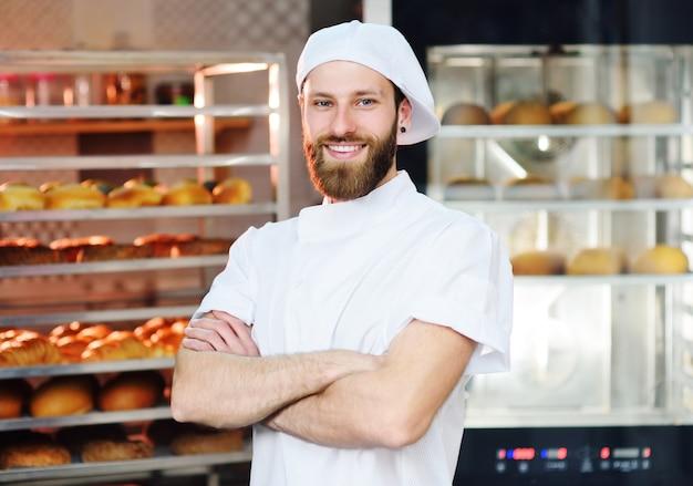 Hübscher männlicher bäcker in der weißen uniform