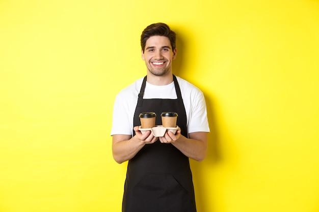 Hübscher männlicher barista, der kaffee zum mitnehmen dient und lächelt, ordnung bringt und in schwarzer schürze gegen gelben hintergrund steht.