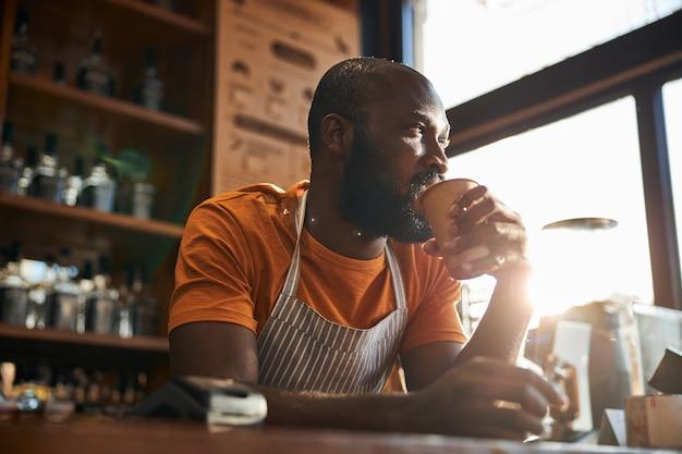 Hübscher männlicher barkeeper, der kaffee bei der arbeit trinkt