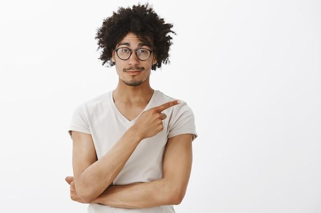 Hübscher männlicher entwickler in gläsern, mann zeigt obere rechte ecke mit erfreutem lächeln, stellen produkt vor