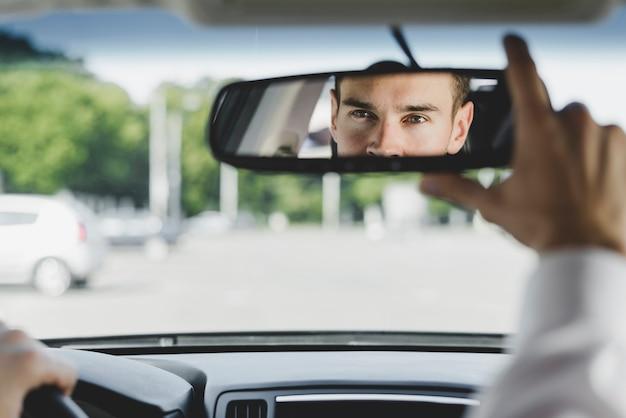 Hübscher männlicher fahrer, der den rückspiegel im auto justiert