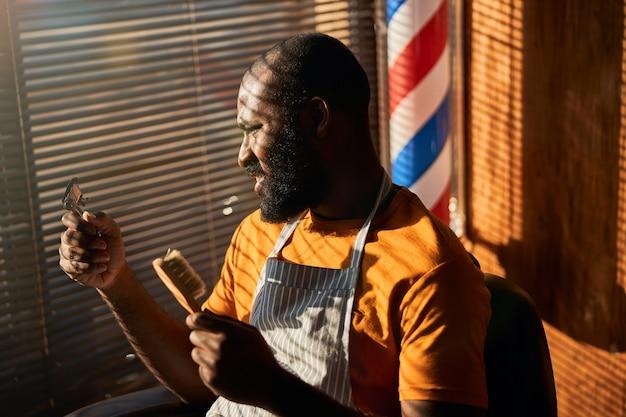 Hübscher männlicher friseur, der haarschneider und bürste hält