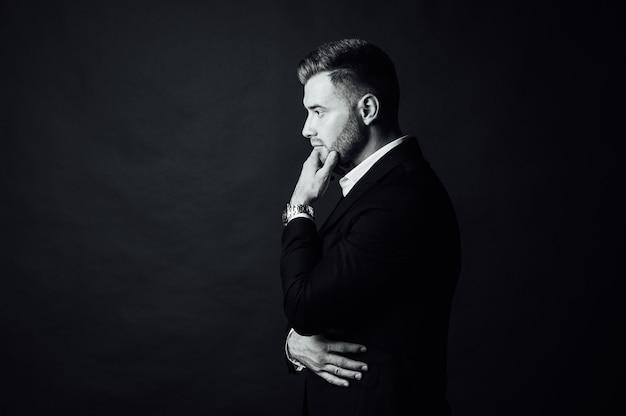 Hübscher männlicher geschäftsmann mit anzug, der in einem fotostudio aufwirft. porträt in halber länge