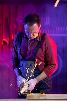 Hübscher männlicher handwerker mittleren alters in der schutzbrille des overalls und in den handschuhen, die metall mit funken im farbigen licht in der garage schleifen