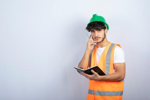 Hübscher männlicher ingenieur im grünen helm mit notizbuch, das über weißer wand steht. hochwertiges foto
