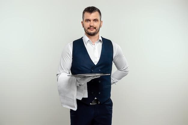 Hübscher männlicher kellner im weißen hemd, der ein silbernes tablett hält. das konzept des servicepersonals, das kunden in einem restaurant bedient.