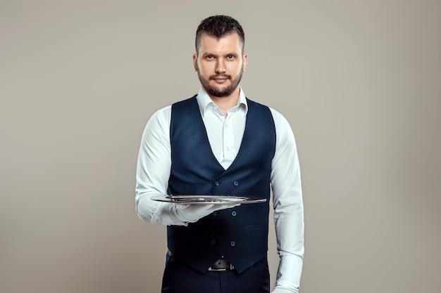 Hübscher männlicher kellner in einem weißen hemd hält ein silbernes tablett auf ausgestreckten armen. das konzept des servicepersonals, das kunden in einem restaurant bedient.