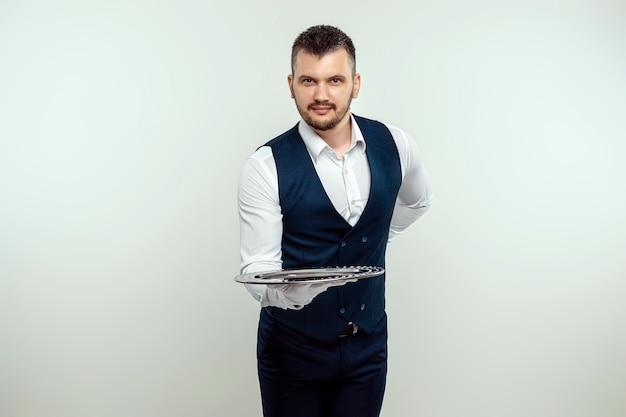 Hübscher männlicher kellner, weißes hemd, hält ein silbernes tablett, hand hinter seinem rücken. konzept des kellners, der kunden in einem restaurant bedient.