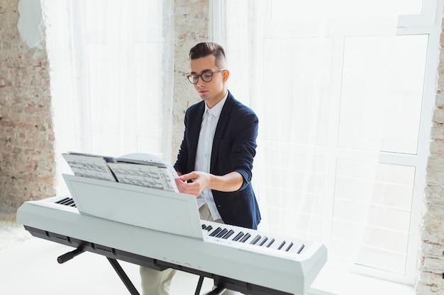 Hübscher männlicher klavierspieler, der die seiten des musikalischen blattes auf klavier dreht