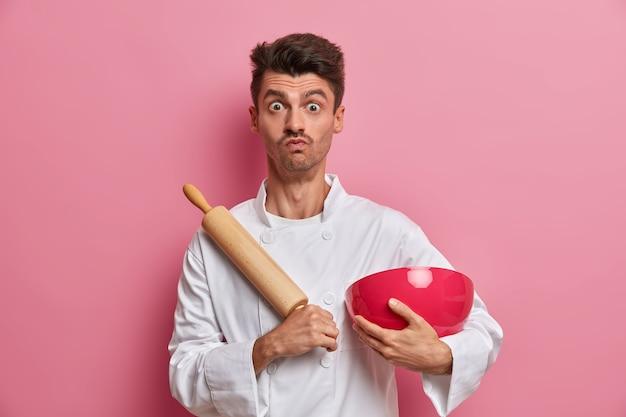 Hübscher männlicher koch mit überraschtem ausdruck, kocht essen in der küche, hält nudelholz und schüssel, bereitet frischen teig zu, trägt weiße uniform