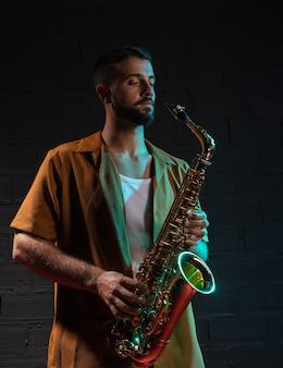 Hübscher männlicher künstler, der ein saxophon hält