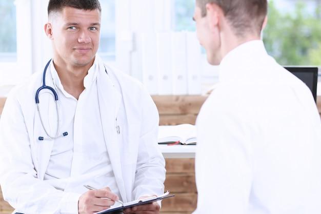 Hübscher männlicher medizinarzt mit klemmbrett