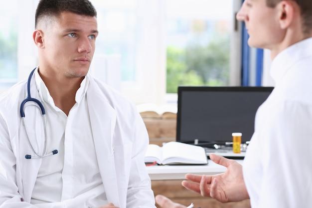Hübscher männlicher medizindoktor mit klemmbrettauflage in den händen überprüfen patienten und schreiben abhilfe vor. runder besuch des prüfungsbesucheraufnahmekrankheitsverhütungs-bezirkes überprüft konzept des gesunden lebensstils 911